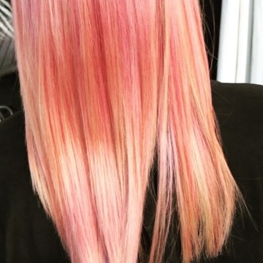 woman with straight pink and peach fruit salad coloured hair