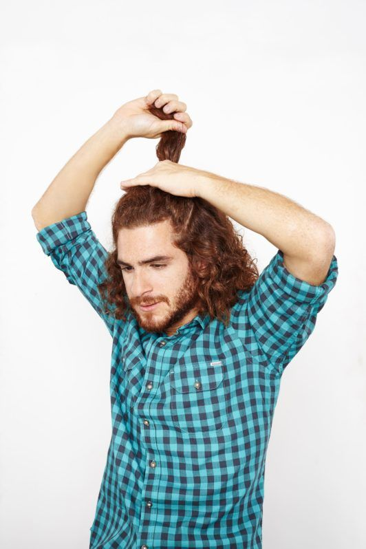 man sectioning curly hair in half
