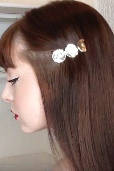 side view of beauty vlogger Mostly Megan with long brown hair and a fringe, wearing a silver hair slide