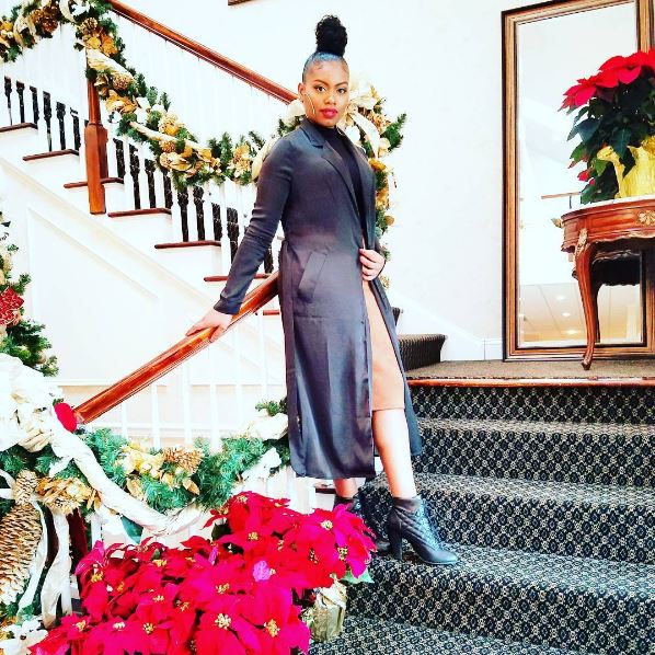 Winter hairstyles for natural hair: Woman with natural hair in a high top bun wearing a long jacket, skirt and boots and posing on a staircase