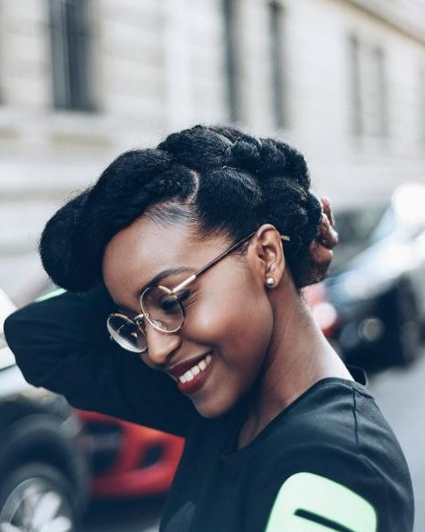 Winter hairstyles for natural hair: Smiling woman with dark natural hair in a twisted pompadour style updo wearing glasses and posing in the street