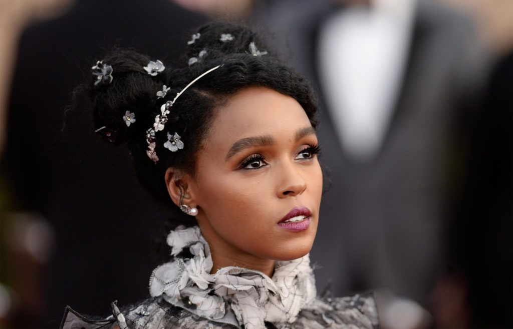 Close up shot of Janelle Monae with a twin bun updo with floral accessories
