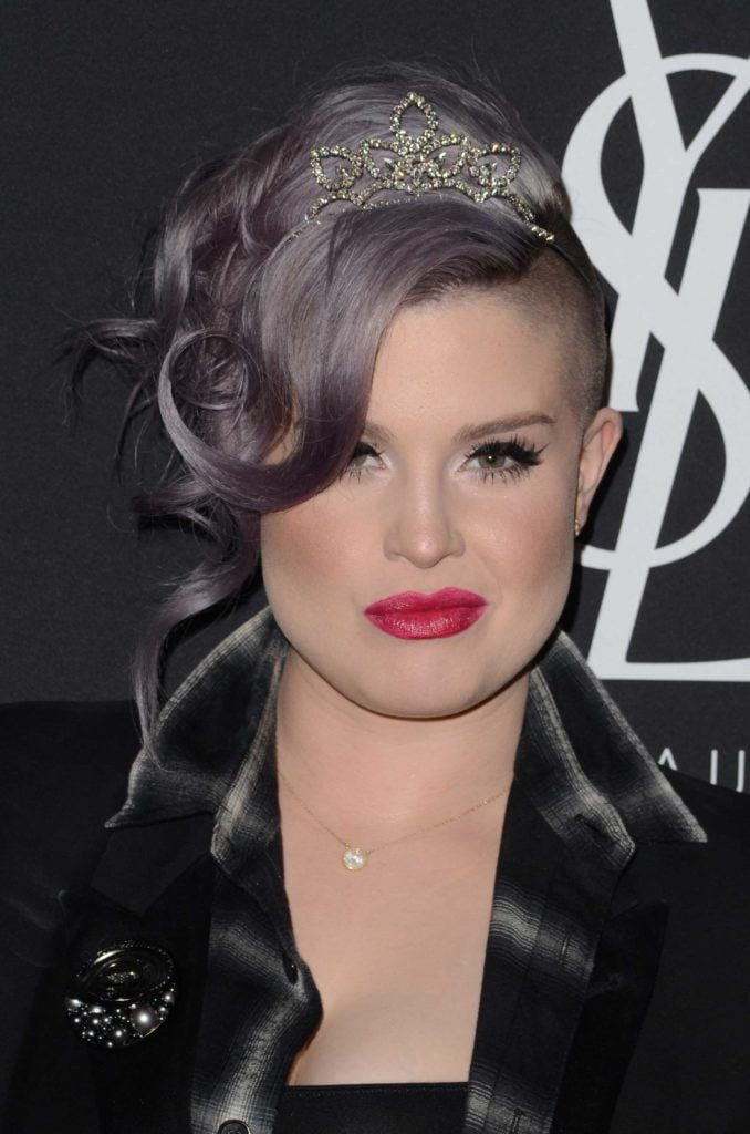 Kelly Osbourne with a purple silver wavy updo on the red carpet wearing a black outfit