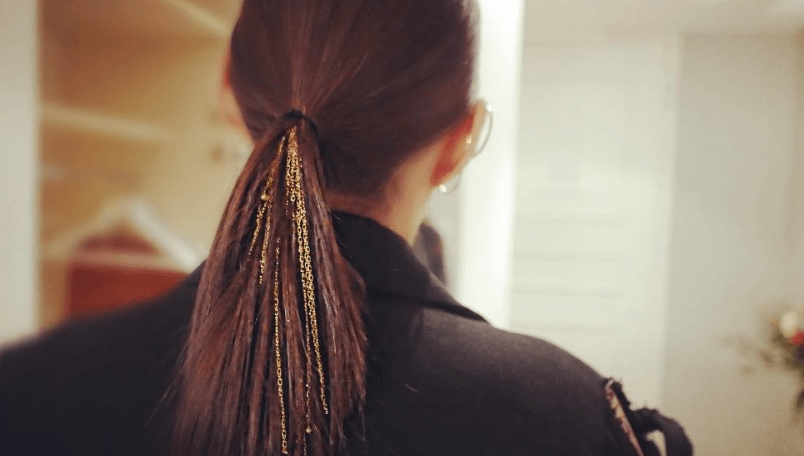 back view of a woman with straight brunette hair worn in a low ponytail with gold chains attached to it