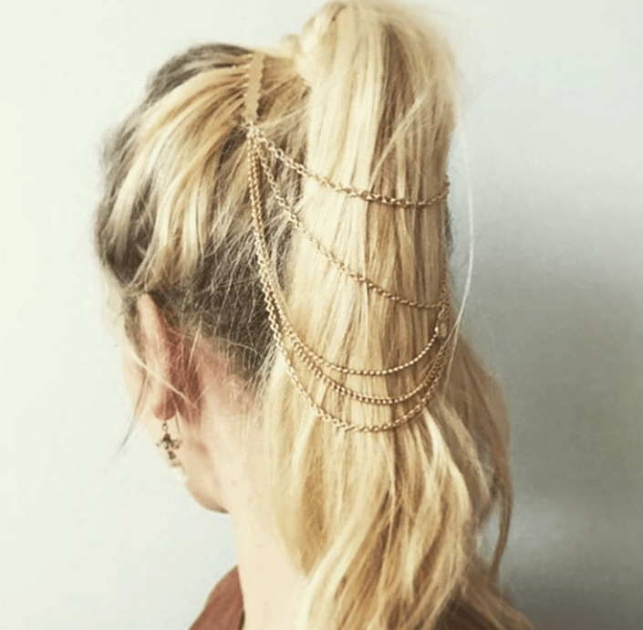 back view of a woman with light blonde hair and dark roots pulled into a high ponytail with gold chains attached