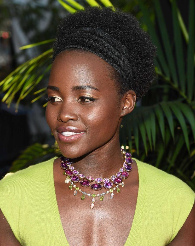 Lupita Nyong'o with afro hairwearing a colourful jewelled necklace and a yellow dress