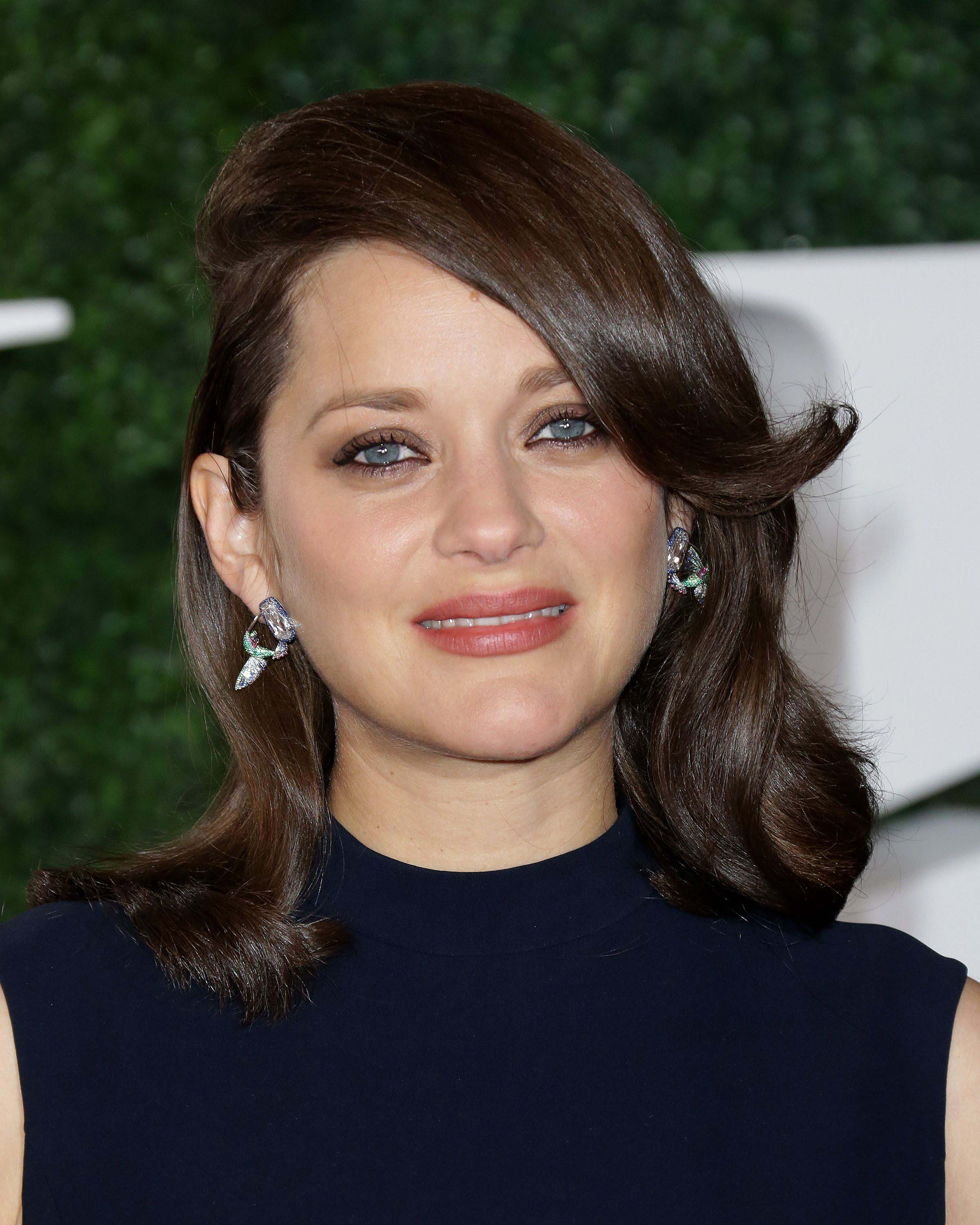 Close up shot of marion cotillard with brown chocolate hair, wearing blue top and drop earrings