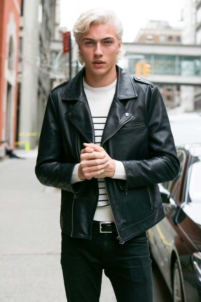 model Lucky Blue Smith on the street wearing a black leather jacket and a white striped top with his platinum blonde hair worn in a curled fringe