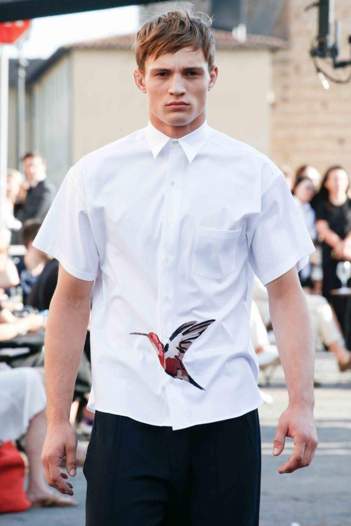 male model on the runway wearing a white shirt with a humming bird printed onto it with his blonde hair styled into a choppy fringe