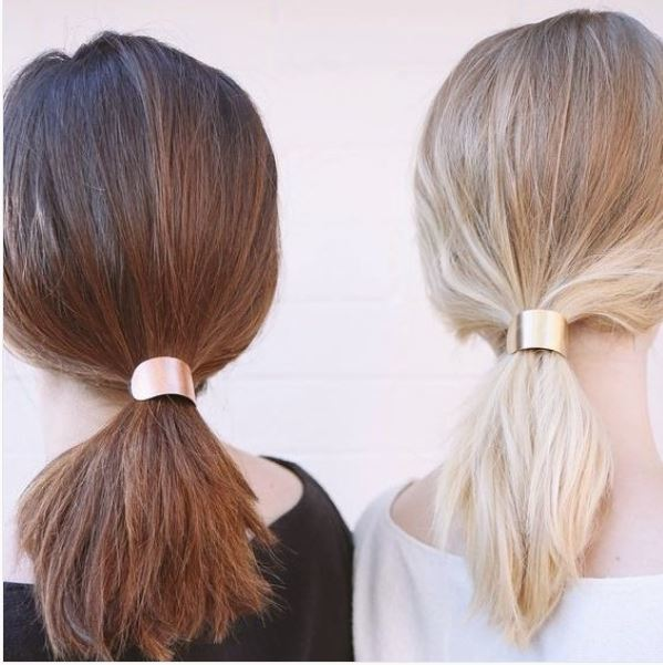 back view of brown hair and blonde hair model with medium length hair styles into low ponytails with gold hair cuffs