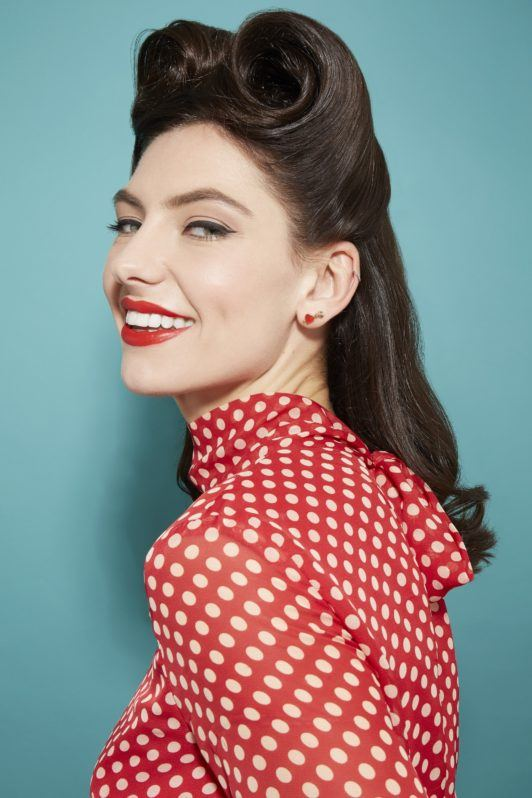 woman with dark brown glossy hair in a retro pin up style looking at the camera smiling and wearing a red and white spotted dress