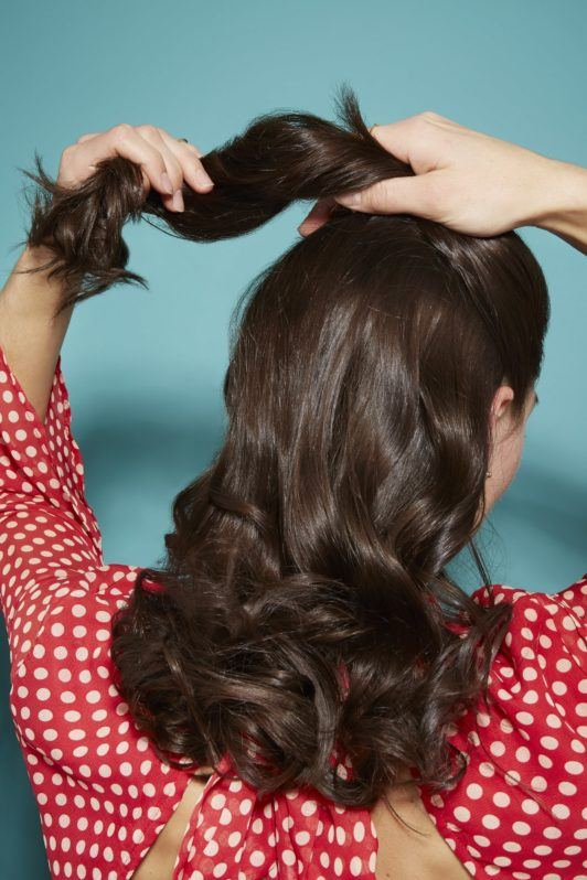 back view of a woman with dark brown glossy hair in loose curls, pulling a section back into a ponytail