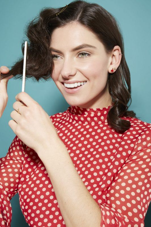 woman with dark brown glossy hair in loose curls looking at the camera smiling and using a comb to backcomb her hair, wearing a red and white spotted dress