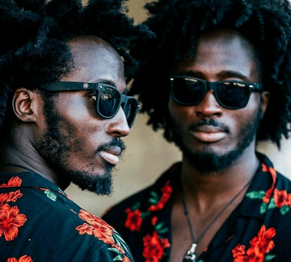 close up shot of two black twins with power afro hairstyle, wearing floral tops and sunglasses