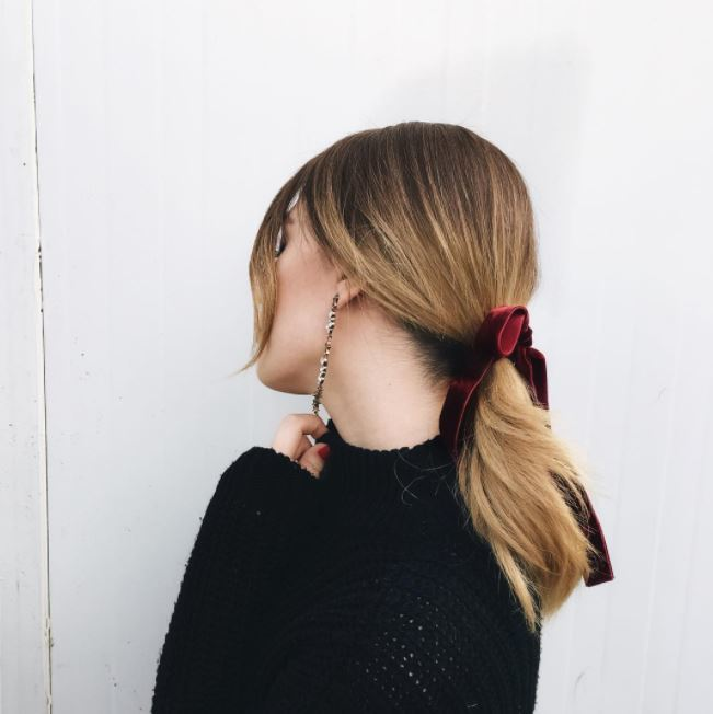 side view of dirty blonde hair in low ponytail with deep red velvet ribbon around base of ponytail