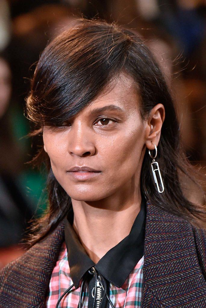 Retro hairstyles: Close up shot of a woman with chocolate brown medium relaxed hair styled into a retro swoop on the Isabel Marant runway