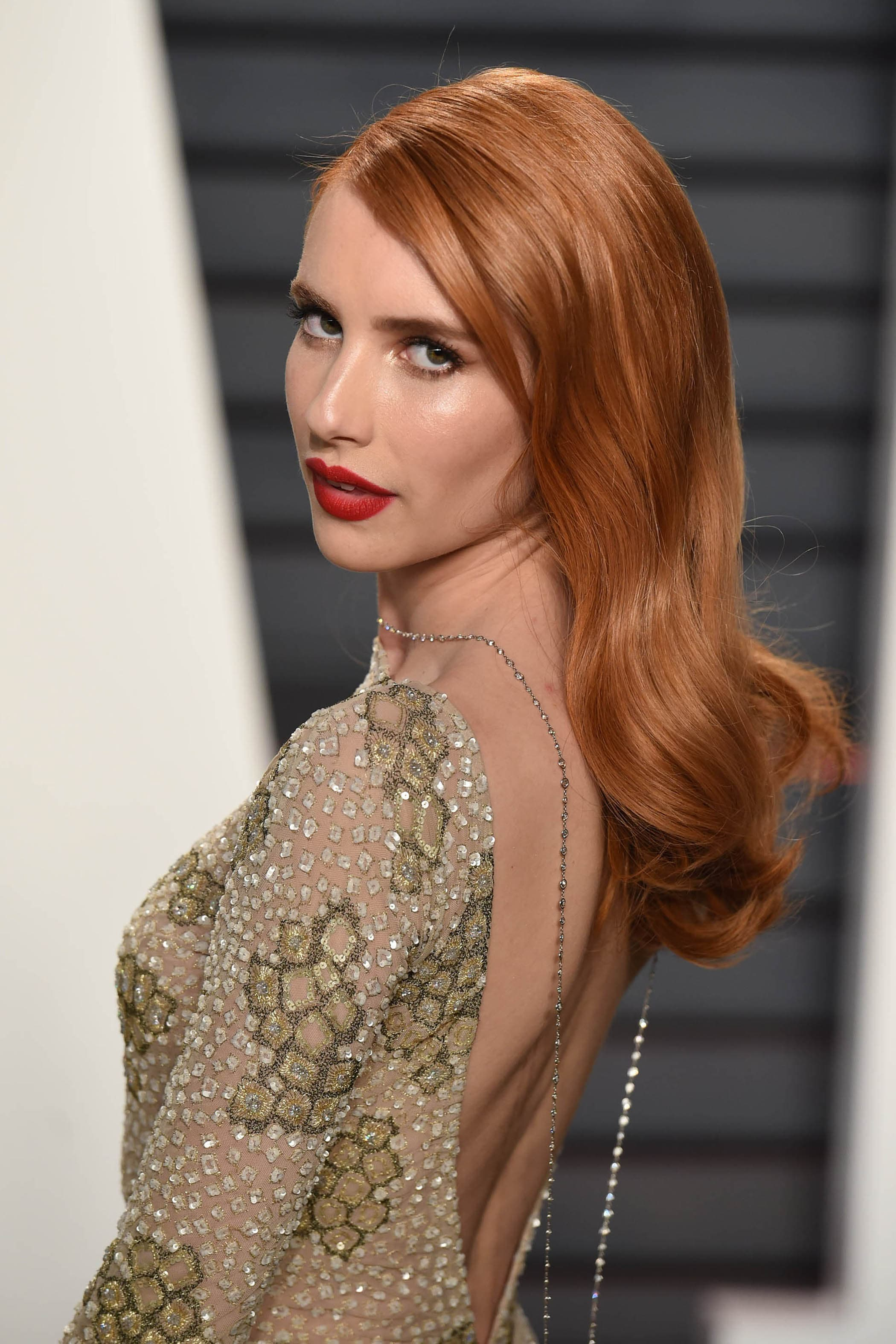Emma Roberts fiery red hair colour with loose curls Oscars 2017