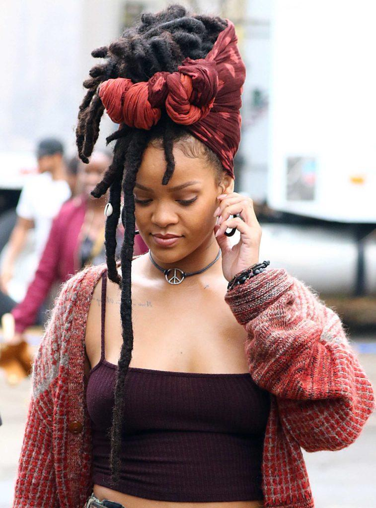 close up shot of rihanna with faux dreadlocks on the set of oceans 8, wearing red top and red cardigan