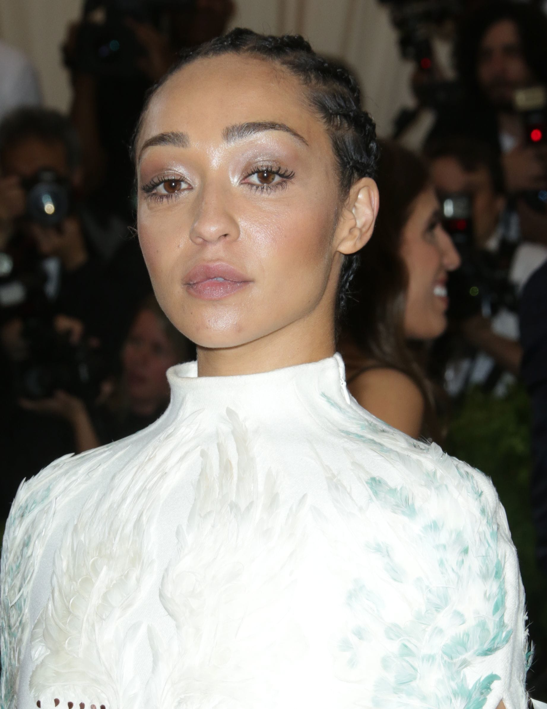 close up shot of ruth negga with cornrows, wearing a white dress on the met gala red carpet