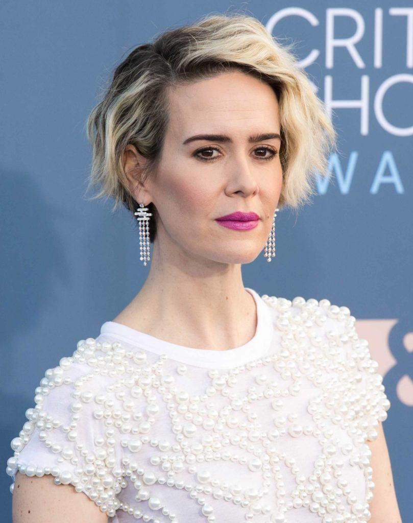 Sarah Paulson on the red carpet with her blonde wavy hair cut into a textured pixie crop