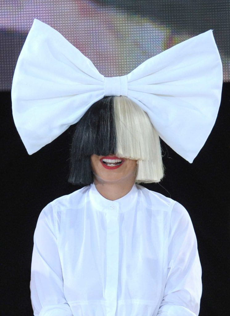 Sia on stage with a black and platinum blonde wig wearing an all white outfit and an oversized bow