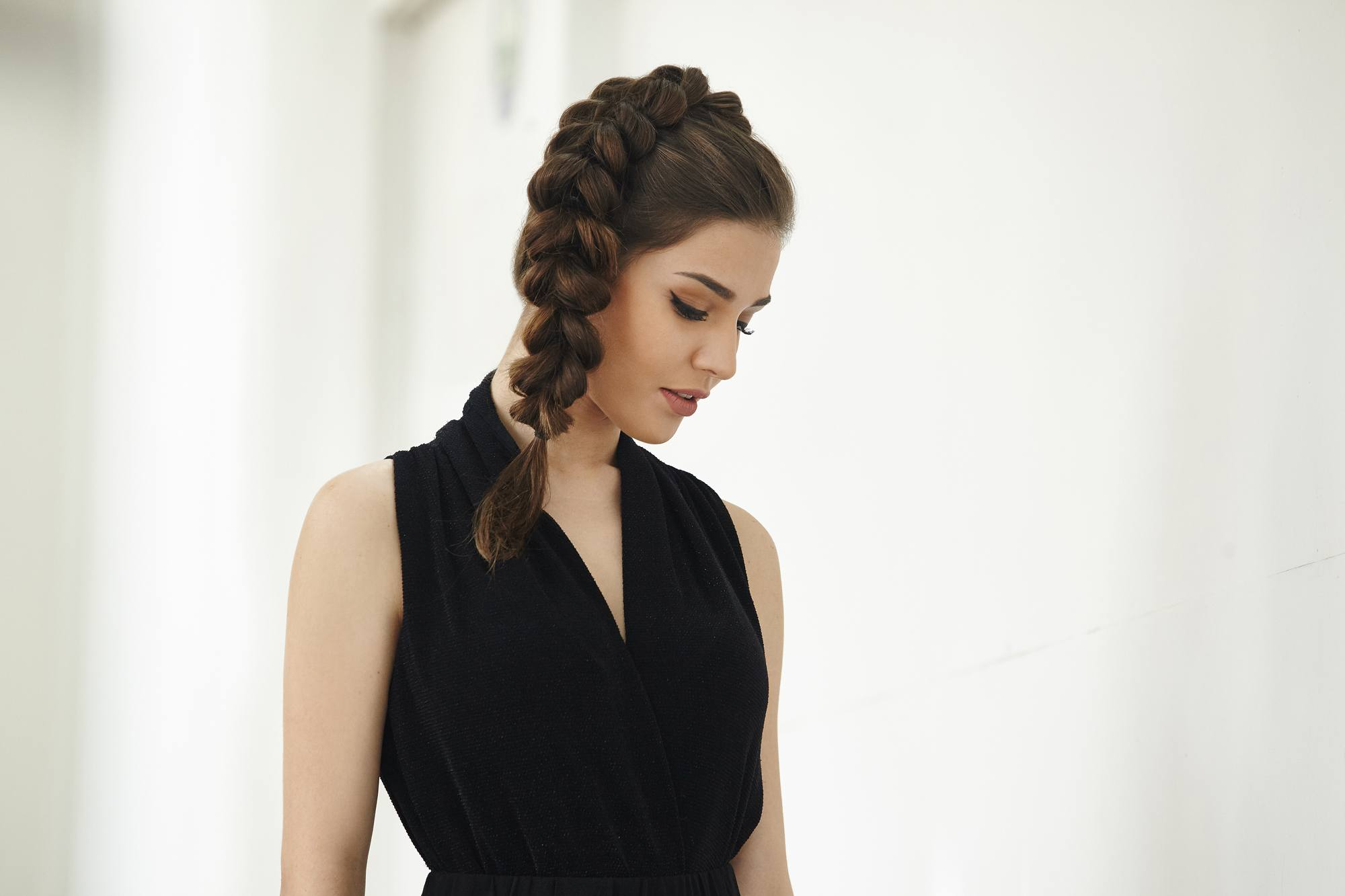 brunette model with a thick side braided ponytail wearing a black v neck dress