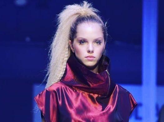 '80s hairstyles: runway model with side high ponytail with crimps wearing purple shiny outfit