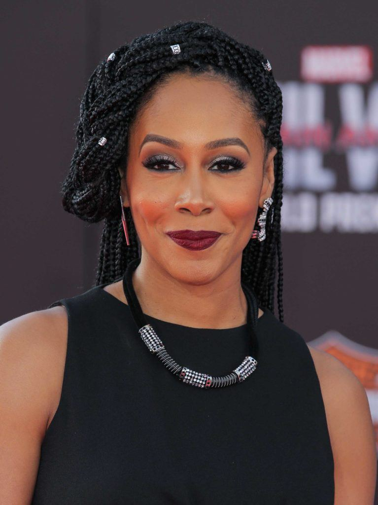 Simone Cook with braids cuffs in her box braids wearing a black dress and necklace on the red carpet