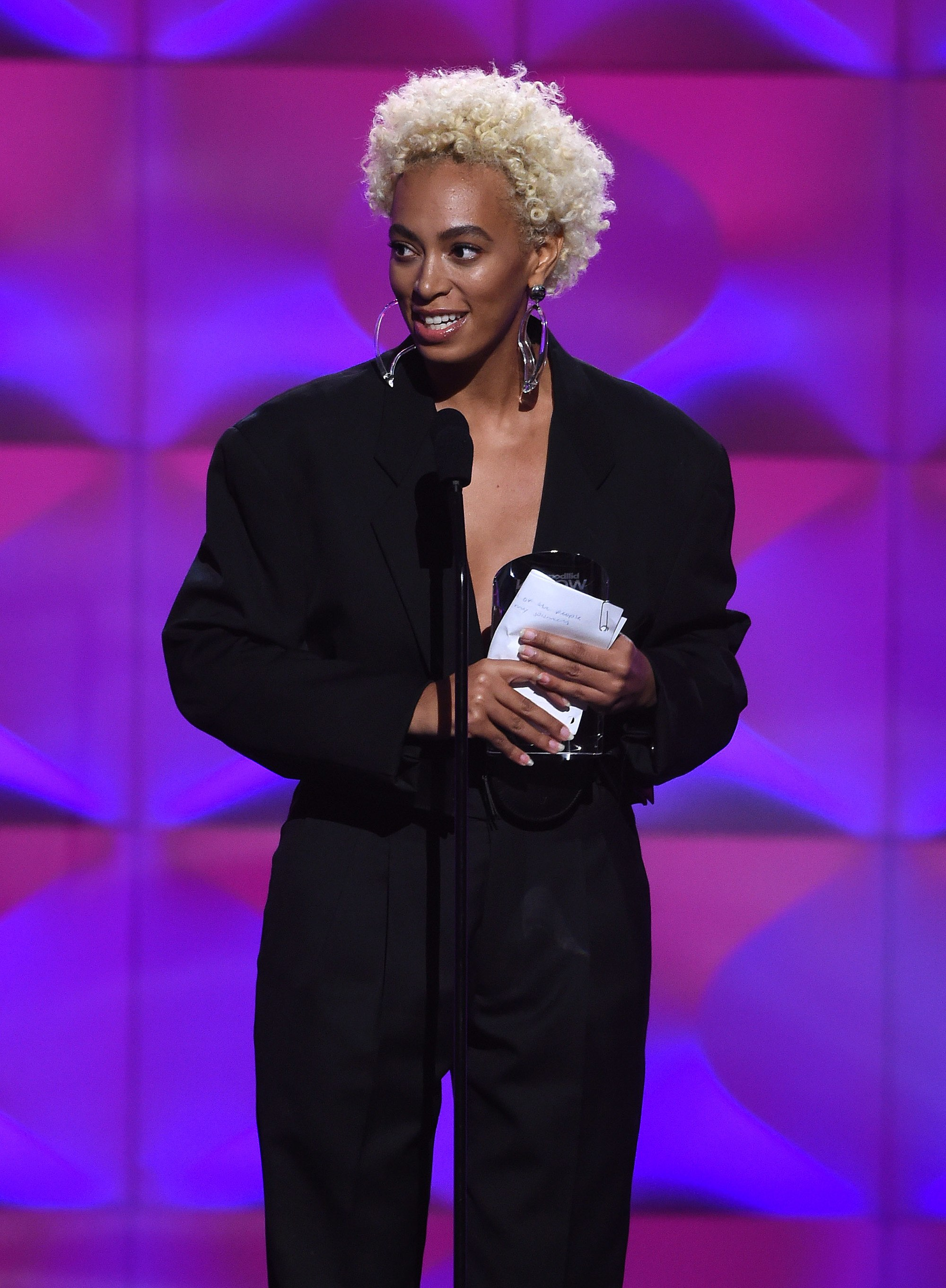 close up shot of solange knowles with blonde afro hairstyle, wearing black jumpsuit and accepting award at the billboard women in music awards