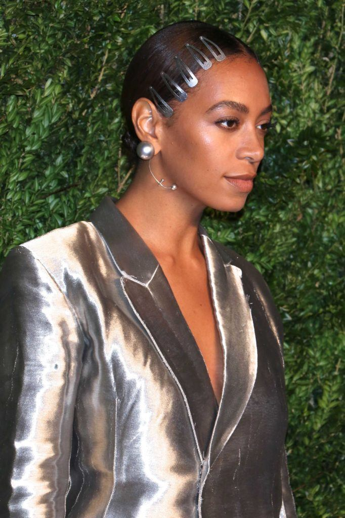 close up shot of solange with sleek low natural bun with hair clips in it, wearing silver on the red carpet