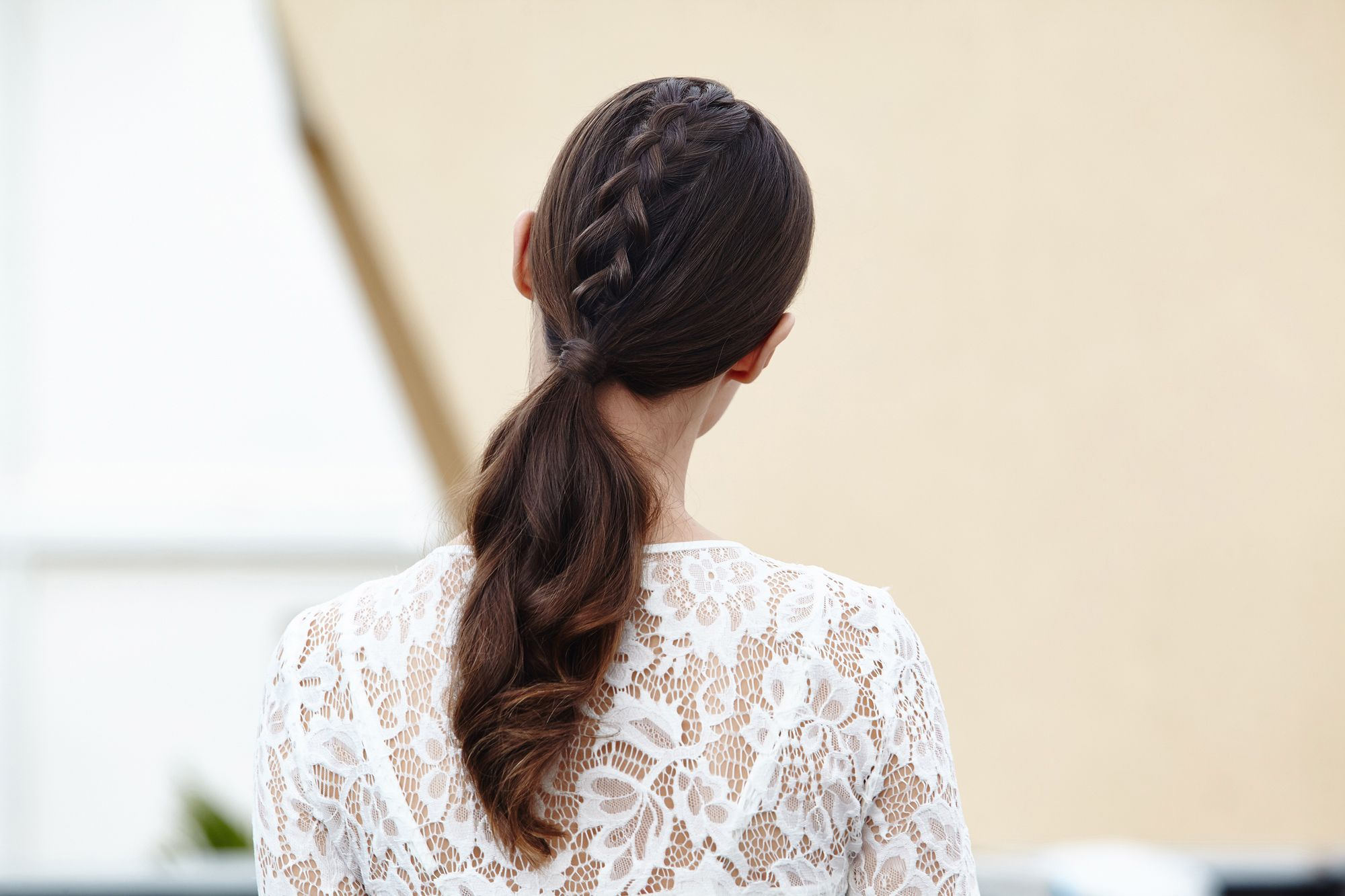 brunette model with a unicorn braid ponytail wearing a white lace top