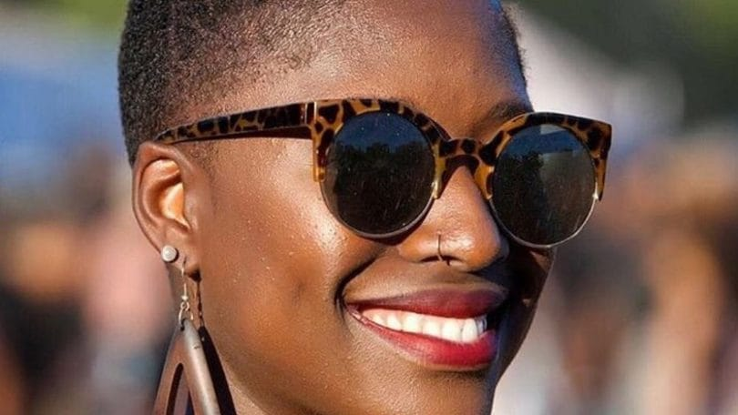 image of a black woman with very short natural hair smiling wearing sunglasses and wooden earrings