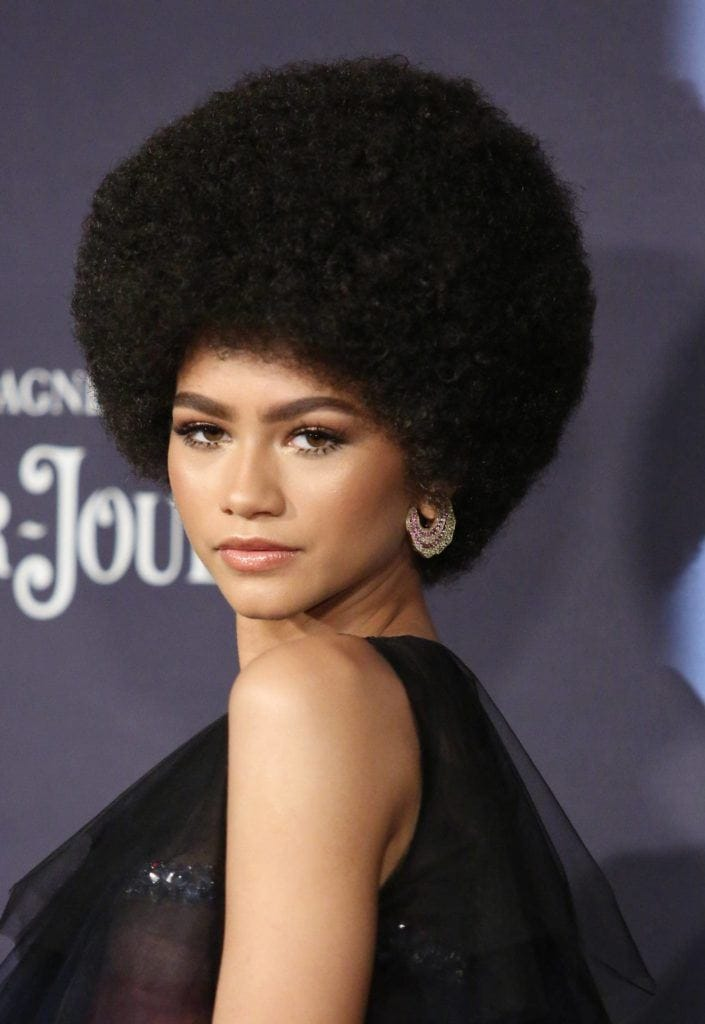 close up shot of zendaya with round afro hairstyle, wearing black dress on the red carpet
