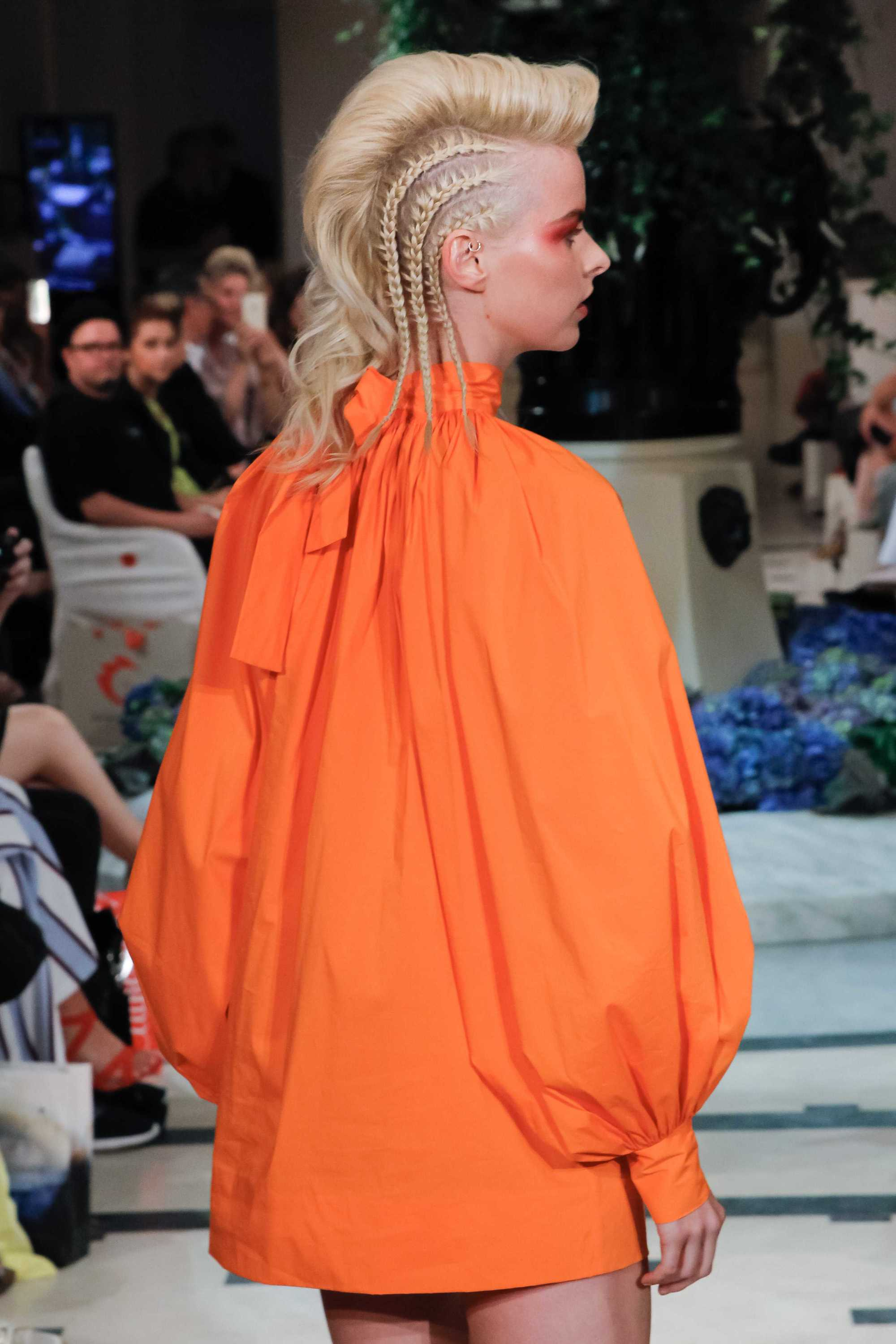 blonde model at the anja gockel show at berlin fashion week with a braided undercut wearing orange