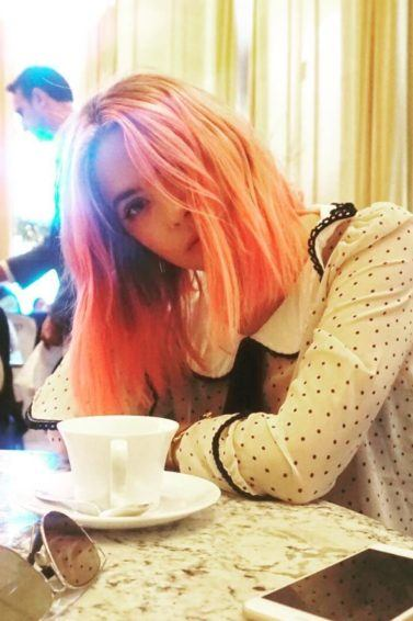 Ashley Benson sat in a restaurant wearing a polka dot blouse with short pink hair with a tea cup and saucer, sunglasses and phone on the table