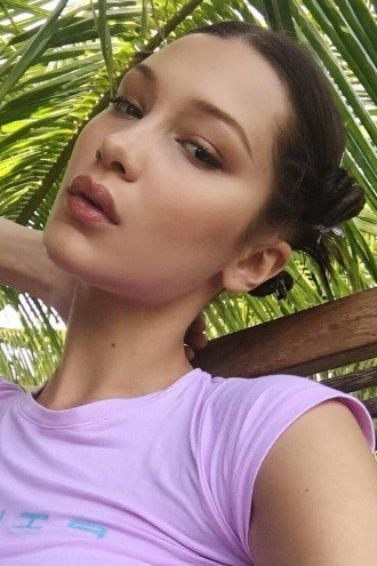 close up shot of bella hadid with a lilac top and a short bun hairstyle, posing next to palm trees