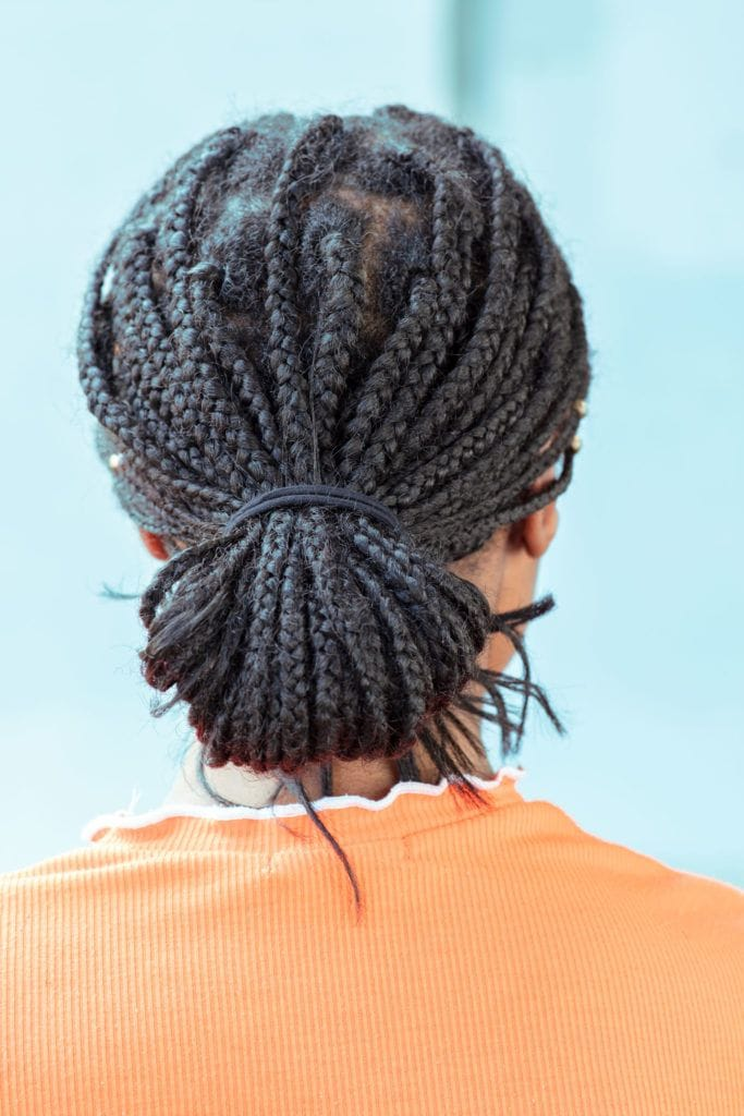black hairstyles: close up shot of woman with dark brown box braids styled into a low bun, wearing a orange top and posing against a blue setting