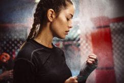 woman with boxer braid hairstyle in gym clothes in a boxing ring