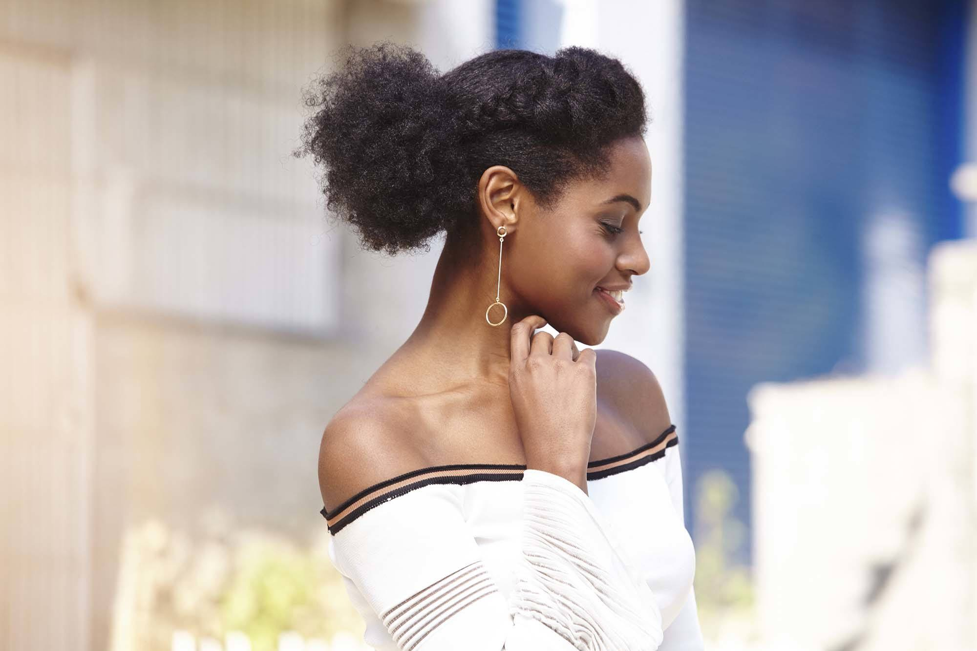 hairstyles for black women: close up shot of a woman with a dark brown afro hair fashioned into a braided, low ponytail, wearing a white bardot top and posing outside