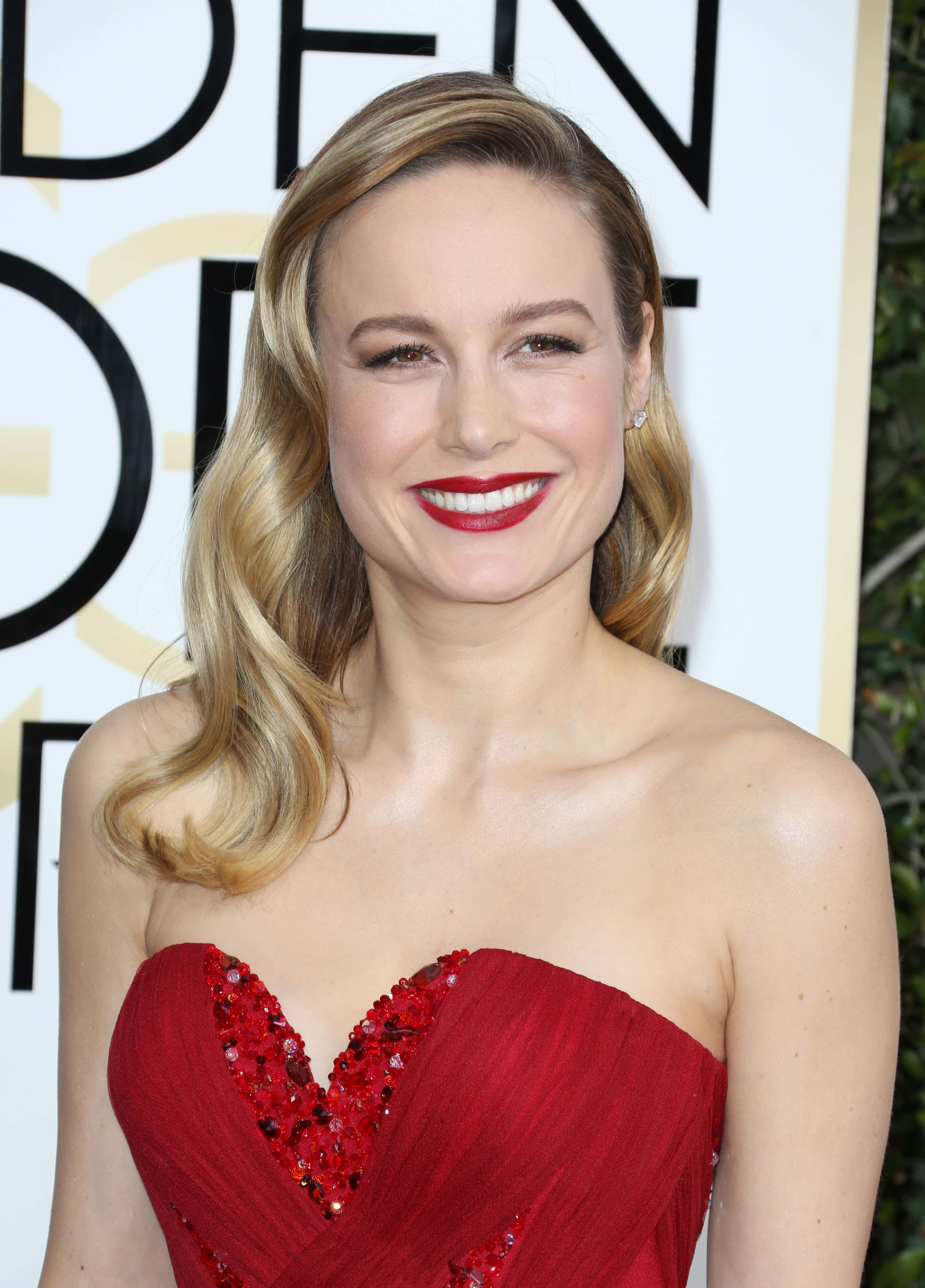 close up shot of Brie Larson with hollywood waves, wearing red dress and posing on the golden globes awards red carpet