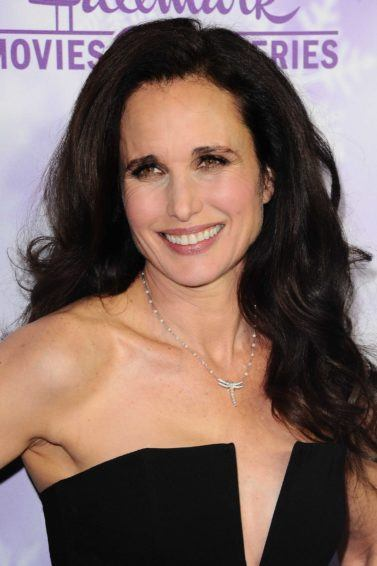 Andie MacDowell on the red carpet wearing a black dress with her wavy dark brown hair styled in a blowout