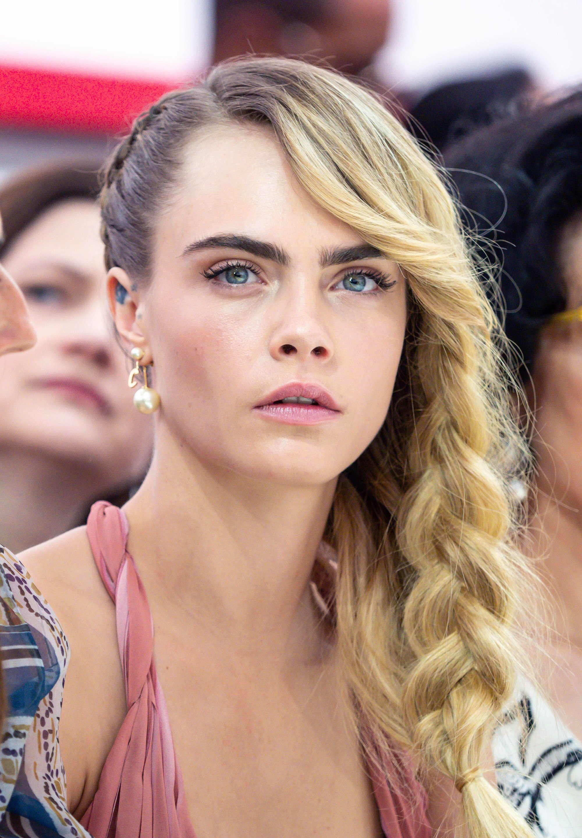 Side hairstyles: Cara Delevingne at Paris Fashion Week AW19 with long blonde hair in a side braid, wearing a pink dress