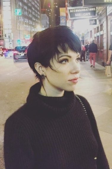 Carly Rae Jepsen with a brown long pixie shag haircut wearing all black