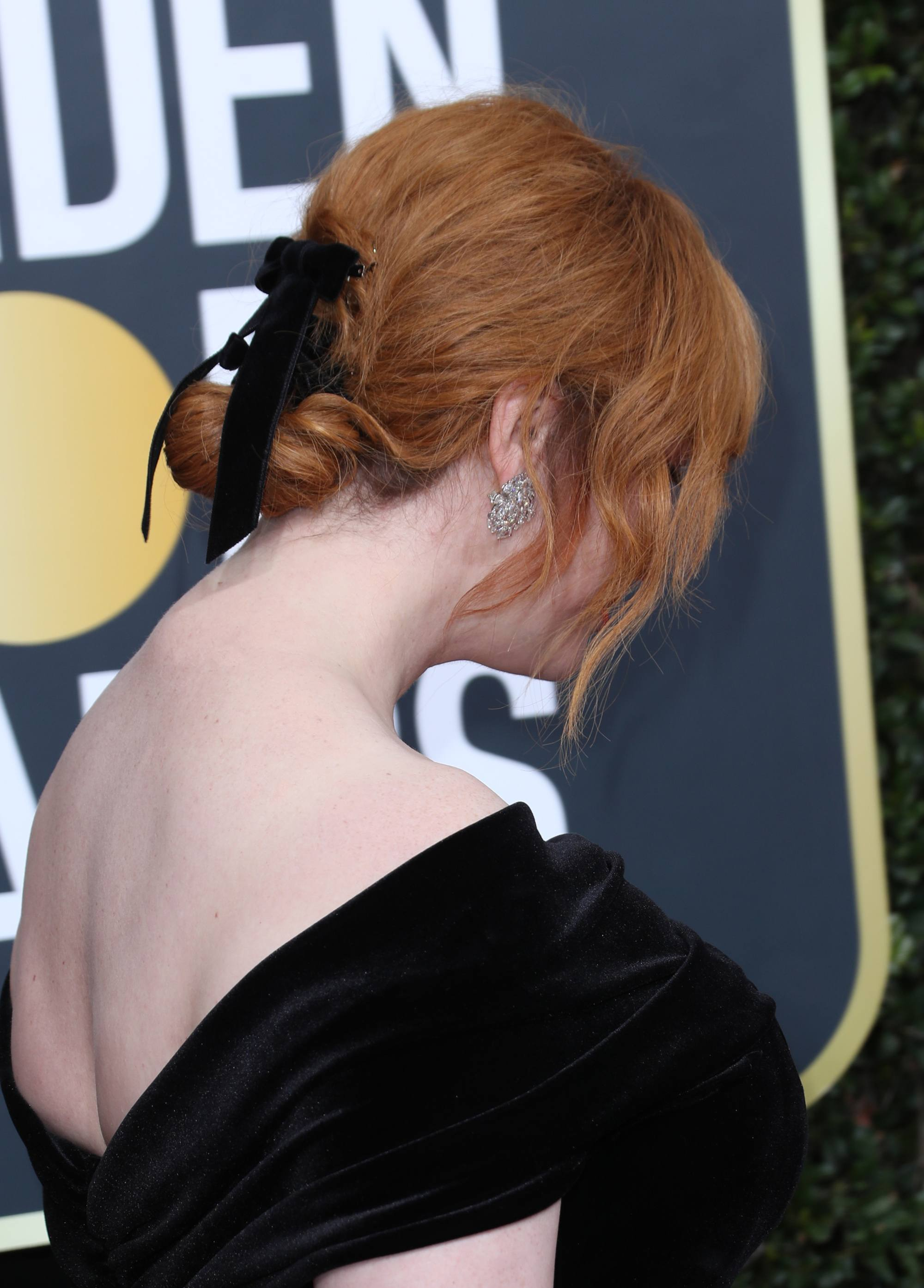 side shot of christina hendricks with low bun hairstyle with bow hair accessory in it