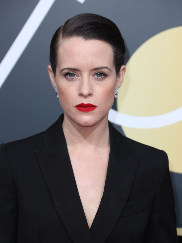 close up shot of claire foy with sleek side parted pixie cut, wearing black suit and earrings, red lipstick and subtle makeup on the golden globes red carpet