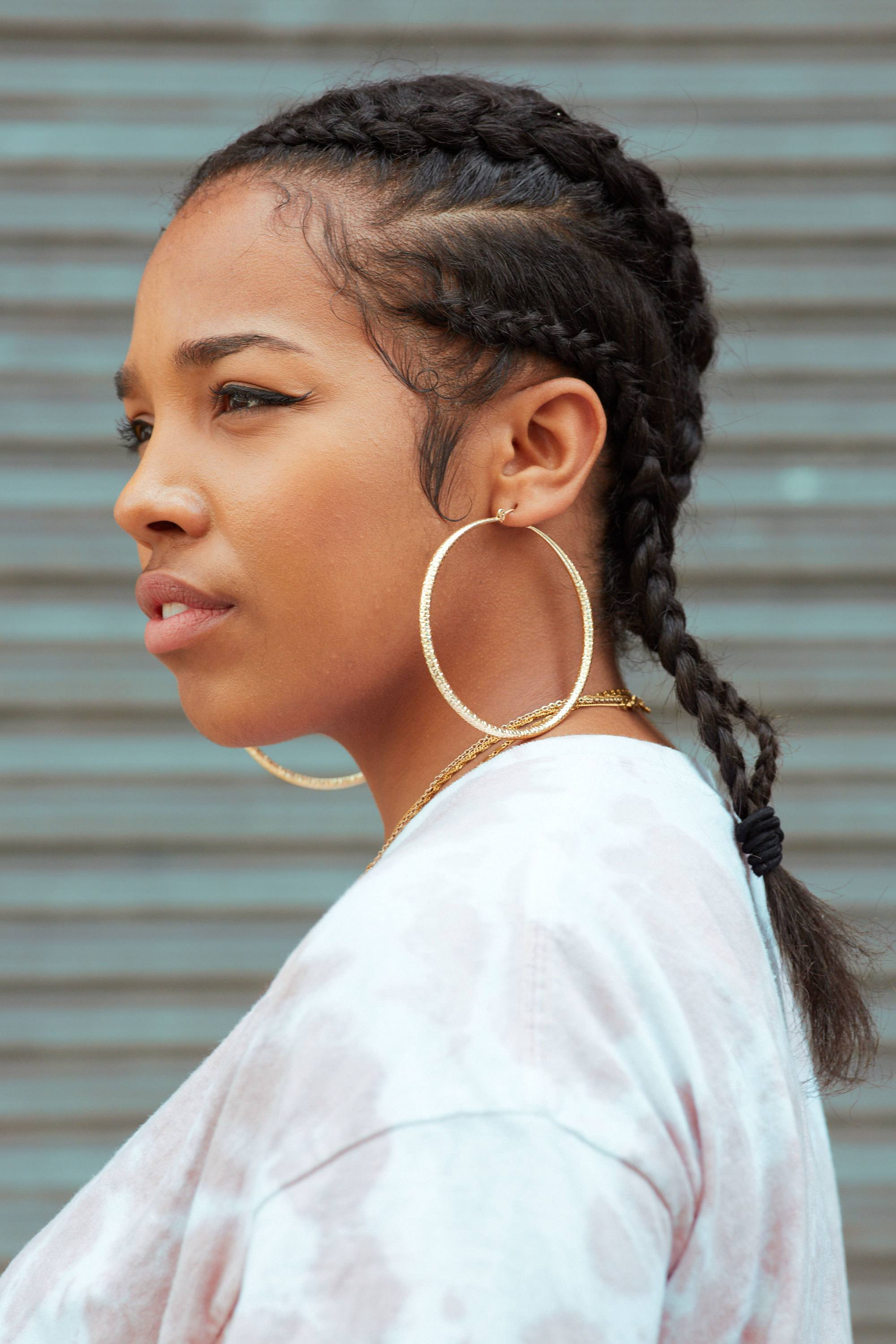 black women hairstyles: close up shot of woman with dark brown hair fashioned into cornrows, wearing big hoop earrings and a white top, posing against a green background