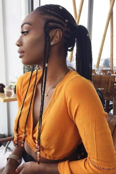instagrammer wearing a yellow cropped blouse with her hair in cornrows into a ponytail with individual braids