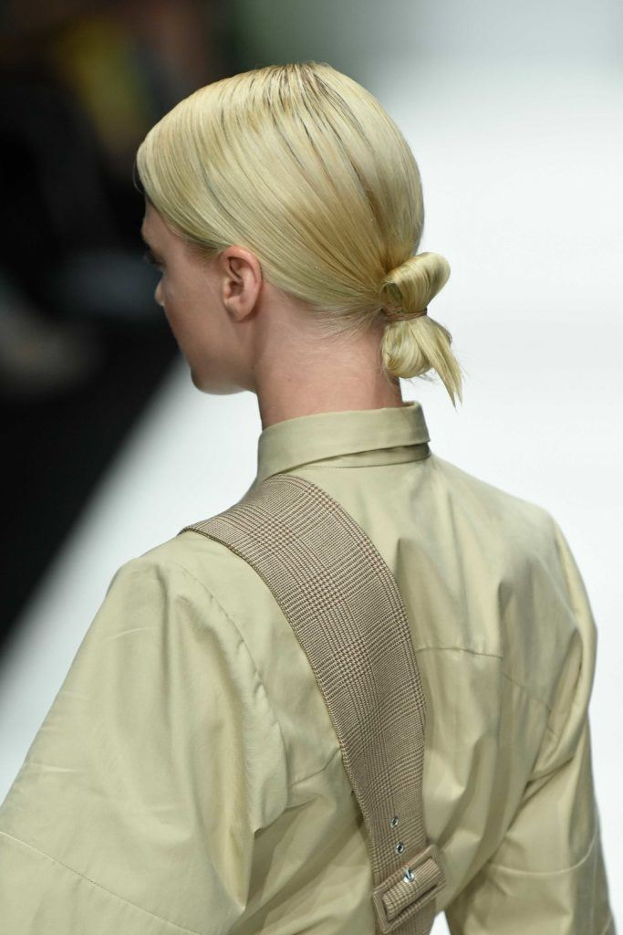 back view of a blonde runway model at the danny reinke show at berlin fashion week with her hair in a low tucked bun
