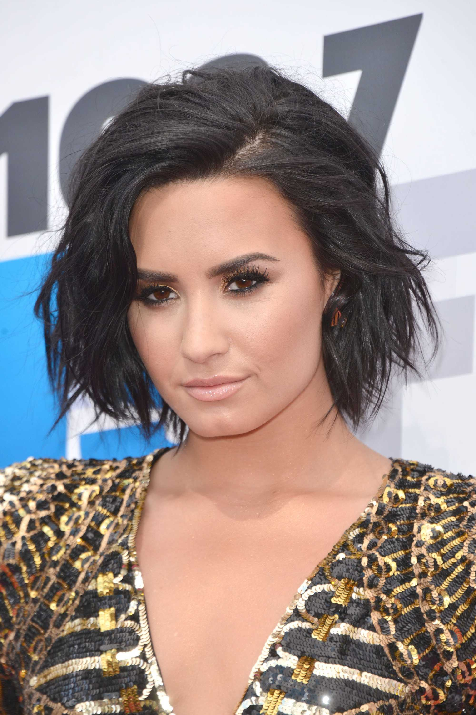 Demi Lovato with textured bob wearing gold outfit