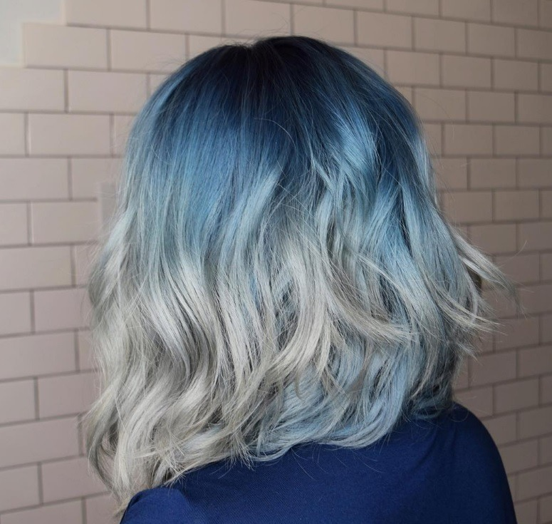 back view of woman with shoulder length denim ombre hair colour finished with waves